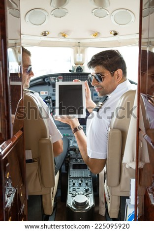 Pilot showing digital tablet to copilot in cockpit of private jet - stock photo