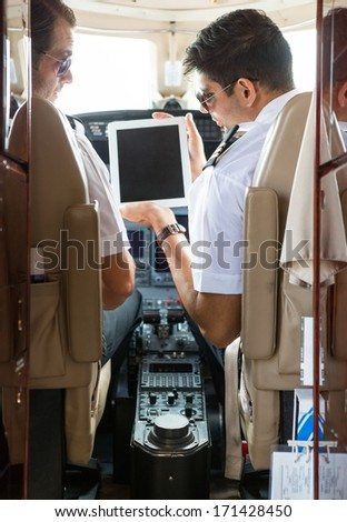 Pilot showing digital tablet to copilot in cockpit of private plane - stock photo