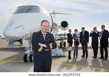 Pilot standing in front of corporate private jet - stock photo