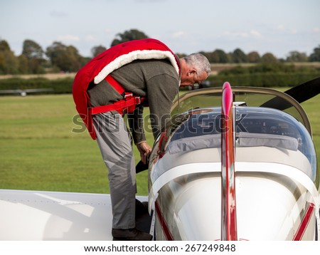 pilot with parachute climbs into his vintage monoplane at the Shuttleworth Collection,Bedfordshire,UK. taken 26/09/2014 - stock photo