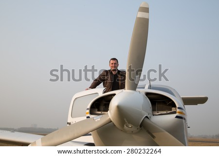 Pilot with the aircraft  after landing. - stock photo