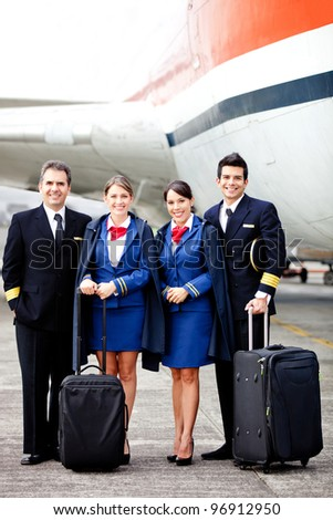 Pilots and air hostesses ready to fly in an airplane - stock photo