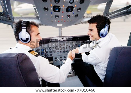 Pilots in an airplane cabin handshaking after a successful flight - stock photo