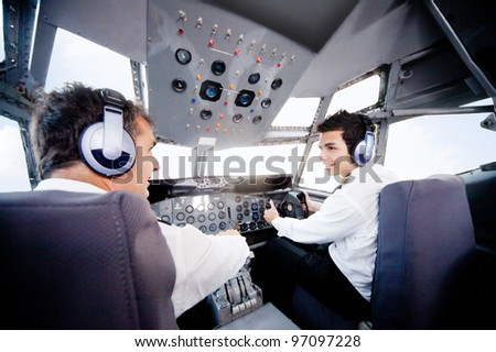 Pilots inside a cabin flying an airplane - stock photo