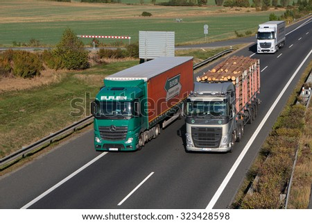 PILSEN, CZECH REPUBLIC - OCTOBER 1, 2015: Dangerous overtaking of two trucks on D5 highway. Cause of frequent car accident. The D5 is important transport connection between West Bohemia and Germany. - stock photo
