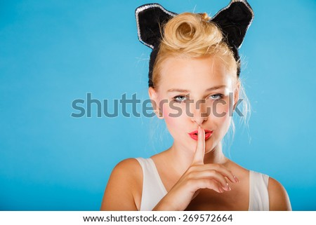 Pin up and retro style. Young smiling woman with black ears on head and finger silence sign symbol on blue background. Studio shot. - stock photo