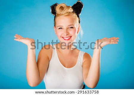 Pin up and retro style. Young smiling woman with black ears on head showing empty hands with copy space blue background. - stock photo