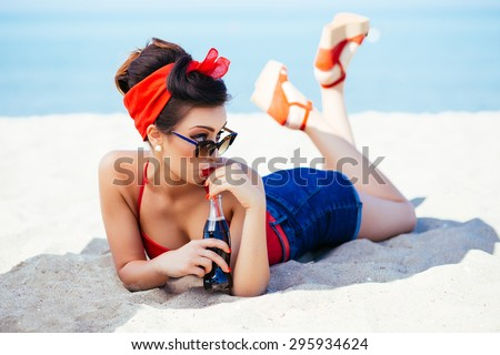 Pin-up at sea drink and watch over sunglasses - stock photo