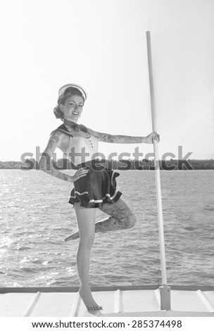Pin-up girl in a sailor suit with a tattoo is on the ship - stock photo