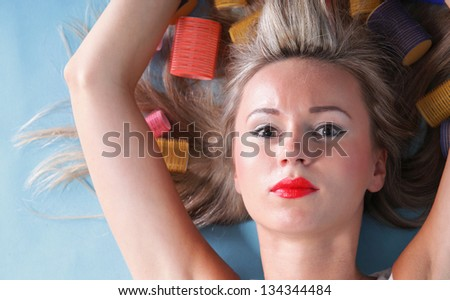 pin up girl retro style portrait woman drying hair with curl-papers hair curlers - stock photo