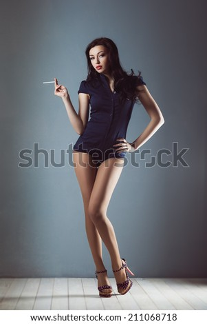 Pin up girl sexy with flying hair in overalls body swimsuit in shoes with cigarette  smoke - stock photo