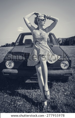 Pin up girl standing in front of retro car on a field. Grayscale image. - stock photo