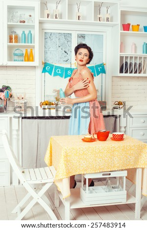 Pin-up girl style. Girl in retro style stands in the kitchen and holding a bottle.