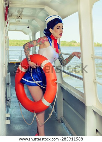 Pin-up girl with the frightened sailor lifeline on board merchant ships - stock photo