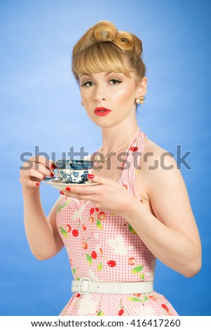 Pin up girl with vintage teacup and saucer - stock photo