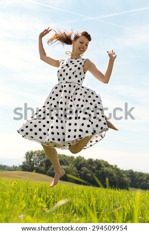 Pin up Girl with white petticoat dress is jumping in the meadow - stock photo