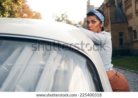 pin-up lady near retro car sunlit background - stock photo