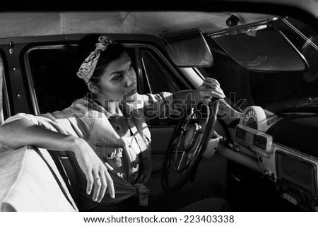 pin-up lady with tattoos in old car wearing jeans shirt - stock photo
