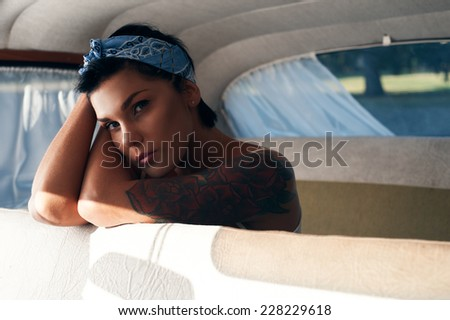 pin-up lady with tattoos in retro car
