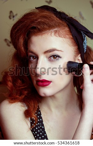 Pin up redhead woman doing her make up routine