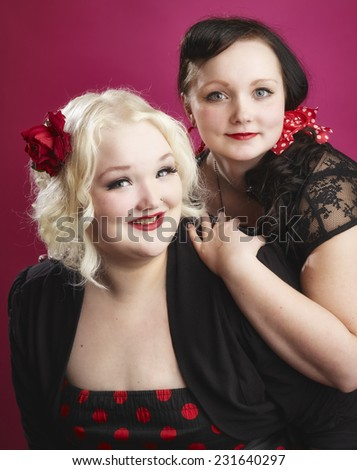 Pin-up sisters posing together and they looks toward the camera, pink background