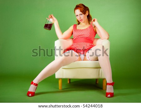Pin-up style girl on the chair drinks whiskey - stock photo