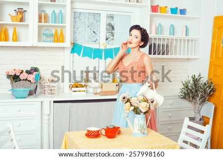 Pin-up style. Girl watering flowers standing in the kitchen in a retro style. - stock photo