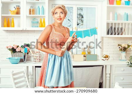 Pin-up style. Girl with a rolling pin stands in the kitchen, look at the ceiling and dreams. - stock photo