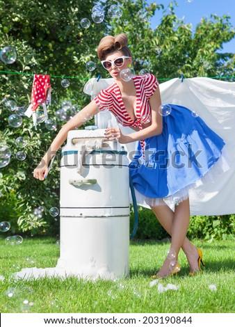 Pin up style photo of woman doing laundry using vintage wringer washing machine - stock photo