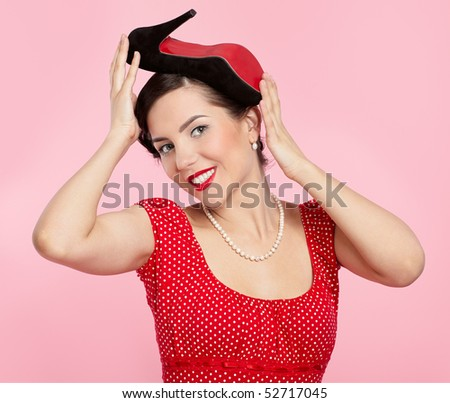 pin-up style portrait of beautiful brunette girl posing with court shoe on her head - stock photo