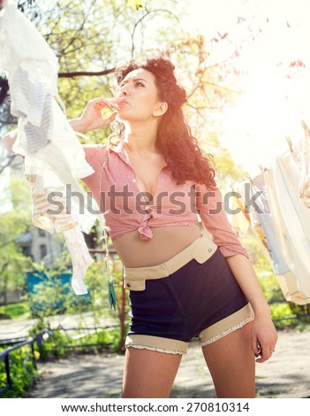 Pin up, vintage style photo of woman doing laundry and smoking - stock photo