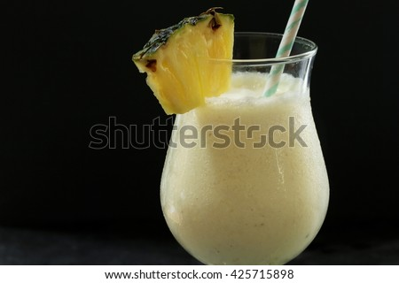 Pina Colada Cocktail - sweet cocktail made with rum, coconut cream or coconut milk garnished with pineapple wedge, selective focus - stock photo