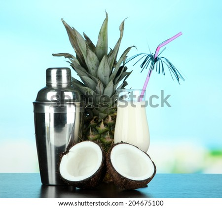 Pina colada drink in cocktail glass and metal shaker, on bright background - stock photo