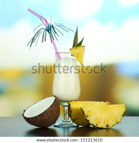 Pina colada drink in cocktail glass, on bright background - stock photo