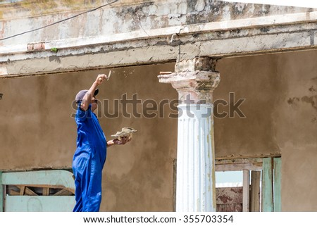 PINAR DEL RIO,CUBA-JULY 3,2015: Cuban bricklayer repairing a classic vintage colonial building. Recovering old architecture is priority. Those beautiful buildings are an attraction that brings dollars