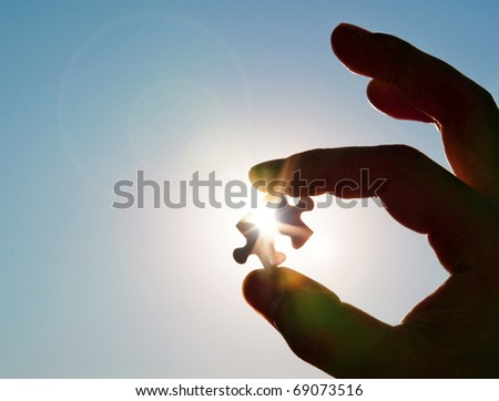 Pinch a piece of the jigsaw puzzle - stock photo