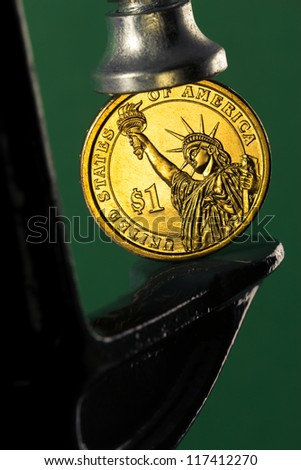 Pinching a golden dollar coin in a c clamp isolated on green background (financial pressure concept) - stock photo