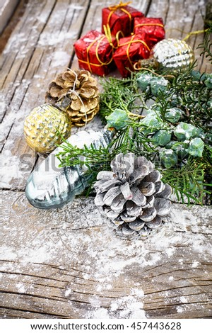 Pine and pinecone Christmas decorations on snowy wooden background - stock photo