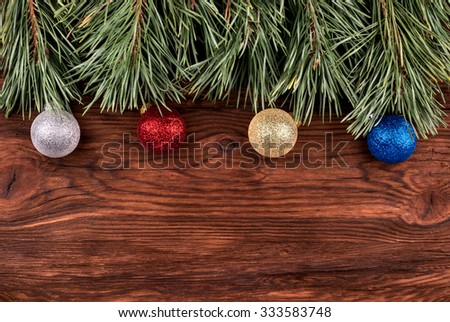 Pine branch with christmas toys on an empty wooden background for an inscription - stock photo
