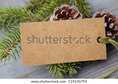 Pine branch with label on wooden background - stock photo