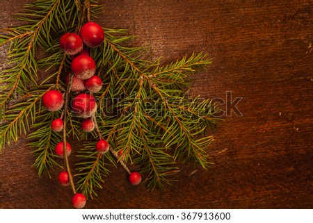 Pine branches with Christmas berries on wooden panels