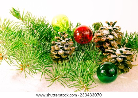 pine cone and christmas ball over green pine branches