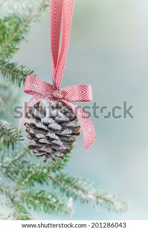 Pine Cone Christmas ornament hung from a Christmas tree with snow. Shot with copy space.