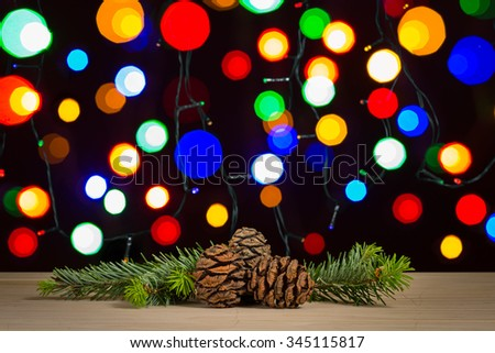 pine cones and branch with defocused lights background
