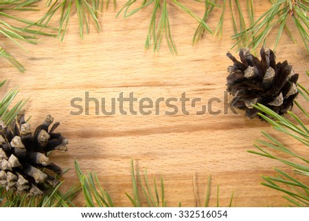 Pine cones and branches lie on the wooden background