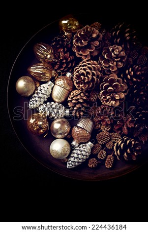 Pine cones and Christmas ornaments on a rustic tray - stock photo
