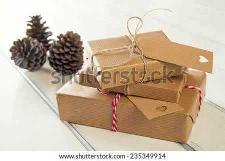 Pine cones and some paper parcels wrapped tied with tags. Christmas gift boxes wrapped with paper kraft and tied with red & white baker's twine on a white wooden table. Vintage Style. - stock photo