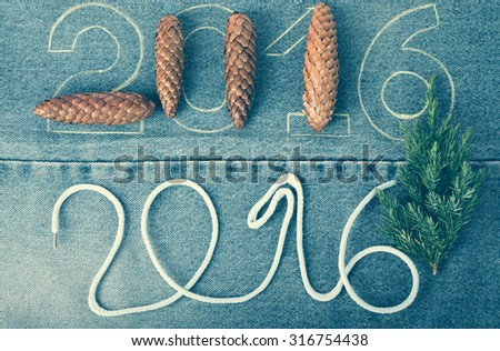 Pine cones, fresh branch of christmas tree and the numbers 2016 of rope and chalk contour on the background of the jeans. Christmas theme. Toned. - stock photo
