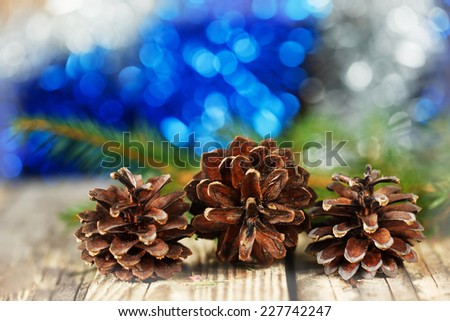 pine cones on wooden board against christmas bokeh background, winter concept