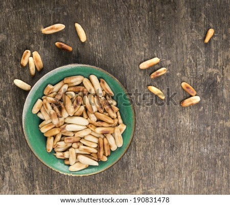 pine nuts on old wooden table, top view - stock photo